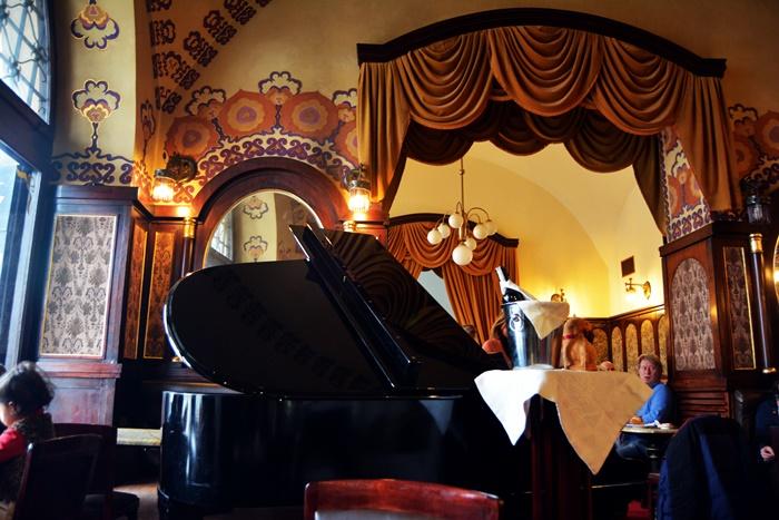 Una foto del interior, donde además del piano, se ven los espectaculares techos y decoración.